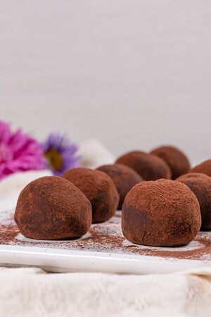 Fine chocolate truffles on white ceramic plate