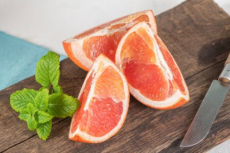 Closeup of fresh juice grapefruit with green sappy leaves of mint, refreshing fruits and herbs on wooden board Stock Photo