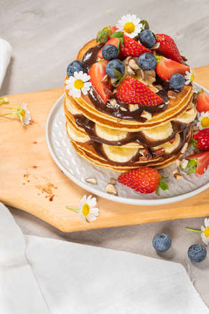 Pancakes with chocolate paste and hazelnuts, banana, strawberry and blueberry