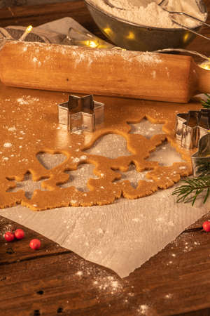 Making christmas gingerbread cookies. Raw dough in shape of gingerbread man, christmas tree, star, snowflakes on paper on tray on rustic table with rolling pin. Preparing for baking