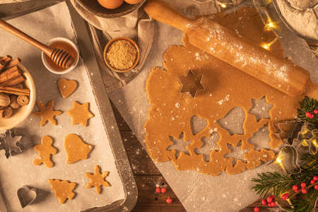 Making christmas gingerbread cookies. Raw dough in shape of gingerbread man, christmas tree, star, snowflakes on paper on tray on rustic table with rolling pin. Preparing for baking Imagens
