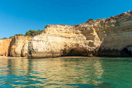 Natural caves and beach, Algarve Portugal. Rock cliff arches of Seven Hanging Valleys and turquoise sea water on coast of Portugal in Algarve region