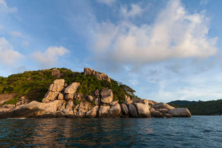 stoned: Stoned island coastline against blue sky with clouds. Koh Tao island, Kingdom of Thailand