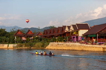 VANG VIENG, LAO P.D.R. - JULY 12 : Unidentified tourists are on long-tailed boat tour in Song River on July 12, 2012 in Vang Vieng, Lao P.D.R.