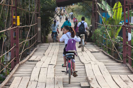 VANG VIENG, LAOS - July 12: young unidentified girl cycling back from school on a Wooden Bridge on July 12, 2012 in Vang Vieng, Laos. Around the villages there are more kids than adults.