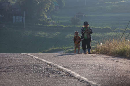 neighbours: Phetchabun province, Thailand - October,26,2012:Mother and son were walking home after work at Phu Tab Berk, Phetchabun province, Thailand. Editorial
