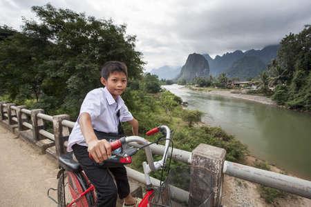Vang Vieng, LAOS - 6 de diciembre de 2012: niño no identificado joven en bicicleta de vuelta a la escuela por un puente de madera. Foto de archivo - 52518024