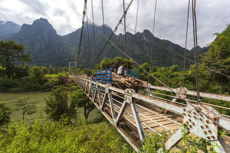 Vang Vieng, LAOS - 6 de diciembre de 2012: El puente colgante que cruza el río Nam Song para el transporte. Foto de archivo - 52518027