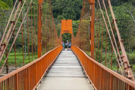 Vang Vieng, LAOS - 6 de diciembre de 2012: turistas toman fotos en el puente rojo. Foto de archivo - 52518030
