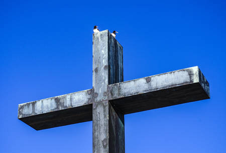Monument. Metal cross of memory. Memorial in the park. Blue sky, birds.