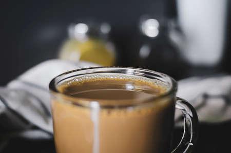 Black fresh coffee with milk in a glass mug. Close up. Kitchen interior.