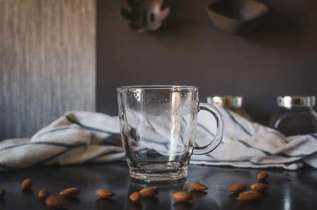 Glass empty mug. Around almonds, staged photo. Kitchen interior.