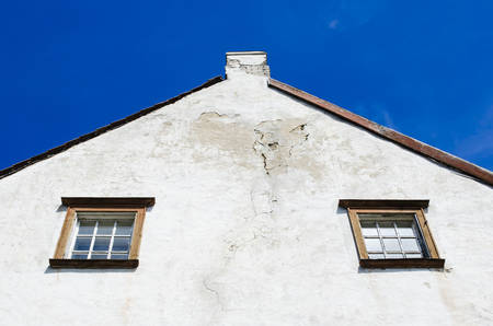 Old wooden Windows of the house. Side white facade of the house. Roof tiles. Bottom view. Estonia.