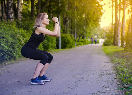 Girl squatting. Healthy lifestyle. Exercises. Sports in the fresh air. Squat. Muscle tone. Speed. Blonde woman in sports clothes black. Photo. The radiance of the sun.