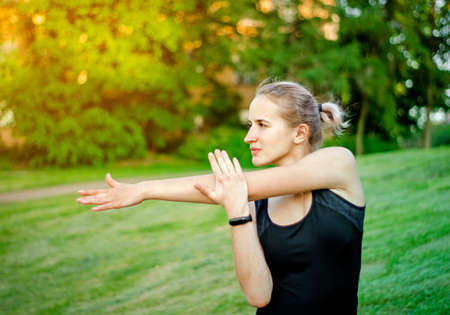 Girl doing a workout in the Park. Healthy lifestyle. Sports activities in the fresh air. Stretching. Muscle tone. Blonde woman in sports clothes black. Photo. The glare of the sun.