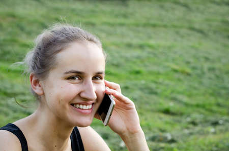 Girl talking on the phone and laughing. Communication through distance. Sitting in the Park. The blonde in sports . Photo. Stockfoto - 129262127
