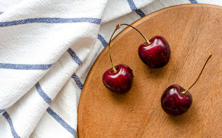 Ripe cherry, top view. On a wooden substrate, striped fabric, towel. Kitchen. Summer berry. The concept of healthy eating.