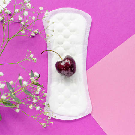 The concept of womens health. Gaskets. Vaginal discharge. Pink background with flowers. Red cherry.