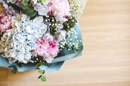 Bouquet of flowers close-up. The view from the top. Standing on the floor, tree. Summer flowers. Peonies, hydrangea and others. Soft focus. Stock Photo