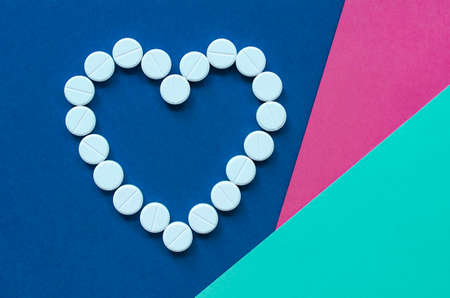 The white heart pills on a colored background. The concept of a healthy life. Heart disease. Arrhythmia, heart failure. Health problem. The impact of the pill on pregnancy. Copy space.