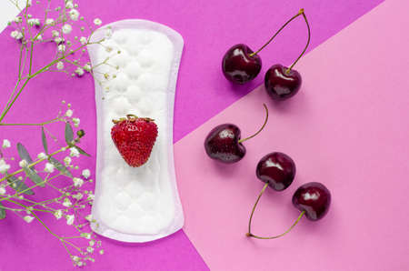 The concept of womens health. Gaskets. Vaginal discharge. Pink background with flowers. Red strawberries and cherries.