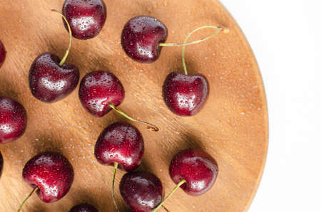 Ripe cherries, top view. On a wooden substrate on a white background. Summer berry. The concept of healthy eating.