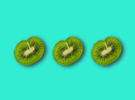 Three halves of sliced kiwi, with shadow. Blue background. The view from the top. Zdjęcie Seryjne