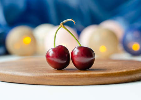 Ripe cherry close-up. Two berries on one branch. Cherry sisters. Blue blurred background. Bokeh. Garlands are burning. Wooden substrate.