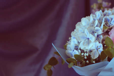 Bouquet of flowers close-up. On a blue background. Still-life. Summer flowers. Peonies, hydrangea and others. Soft focus.