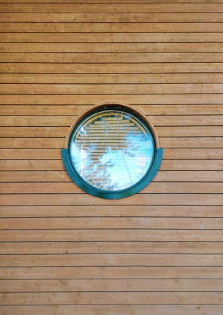 Round window. Wooden house. Wood texture. Reflection of the sky and trees. Modern architecture.