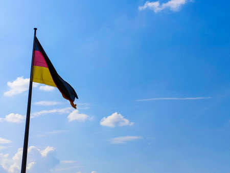 German flag. Against the background of blue sky. Develops in the wind. Zdjęcie Seryjne - 130643696