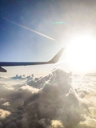 The view from the airplane window. Blue sky and clouds. The sun shines brightly. Morning. Passenger photo. Zdjęcie Seryjne - 131577606
