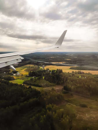 The view from the airplane window. The plane is landing. Visible land, forest, houses. Passenger photo. Stock Photo