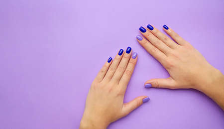Stylish trendy women's manicure. Blue and lilac color gel Polish. The view from the top. Care. Female hand. Lilac background. Archivio Fotografico