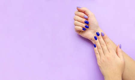 Manicure da donna alla moda alla moda. Smalto gel color blu e lilla. La vista dall'alto. Cura. Mano femminile. Sfondo lilla.