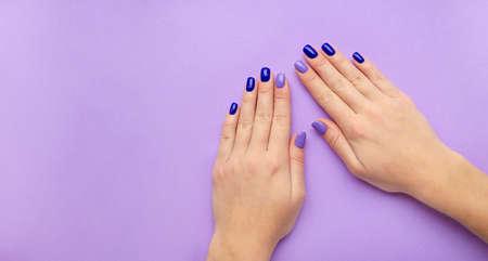 Manicure da donna alla moda alla moda. Smalto gel color blu e lilla. La vista dall'alto. Cura. Mano femminile. Sfondo lilla. Archivio Fotografico