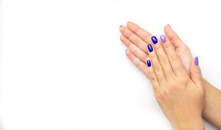 Manicure da donna alla moda alla moda. Smalto gel color blu e lilla. La vista dall'alto. Cura. Mano femminile. Sfondo bianco. Isolato.