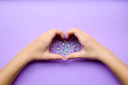 Girl holding hands with heart. Stylish trendy women's manicure. Care. Female hand. Lilac background with sequins. Archivio Fotografico
