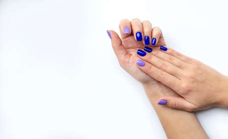 Stylish trendy women's manicure. Blue and lilac color gel Polish. The view from the top. Care. Female hand. White background. Isolated.