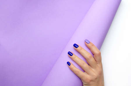 Stylish trendy women's manicure. Blue and lilac color gel Polish. Care. Female hand. Lilac background.