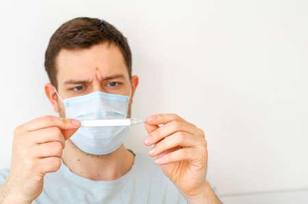 Coronavirus. Quarantine. A man measures the temperature. Heat. In the mask. Coronavirus pandemic in the world.