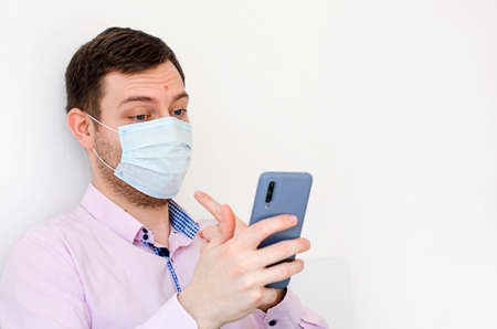 Coronavirus. Quarantine. A man in a shirt in a protective mask. Communication with family through a video call. Shows that he is wearing a mask. Virus protection. Coronavirus pandemic in the world.