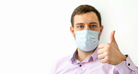 Coronavirus. Quarantine. A man in a shirt in a protective mask. Showing thumbs up. Virus protection. Coronavirus pandemic in the world.