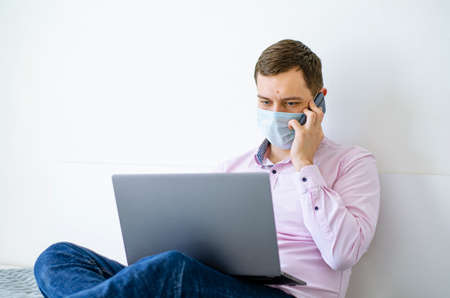 Coronavirus. Quarantine. A man in a shirt and jeans solves work issues remotely. In the mask. Documentation. Laptop and phone. Coronavirus pandemic in the world. Zdjęcie Seryjne
