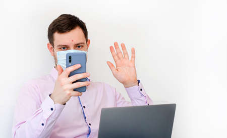 Coronavirus. Quarantine. A man in a shirt in a protective mask. Communication with family through a video call. Virus protection. Coronavirus pandemic in the world.