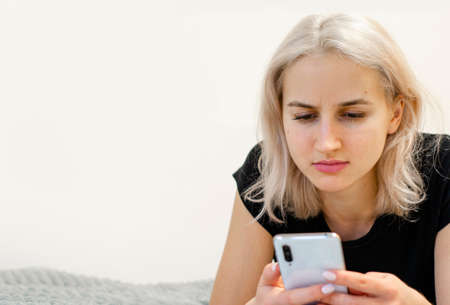 The girl reads bad news on the phone. Social networks.