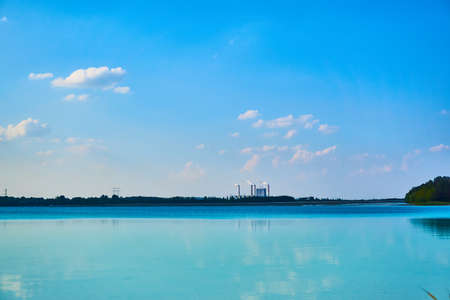 Chimneys of powerhouse surrounding of blue sky and calm peaceful lake