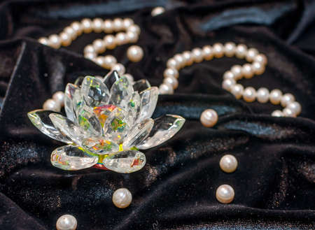 Colorful crystal lotus with pearl necklace on the black velvet
