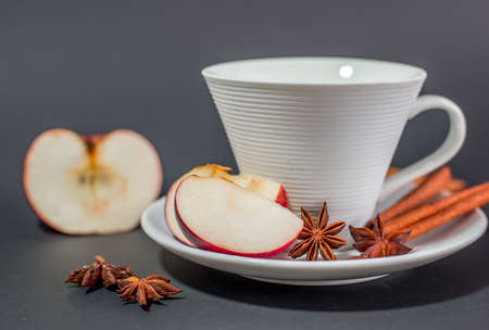 christmas perfume: Cup of tea with cinnamon, anise and apple - black background