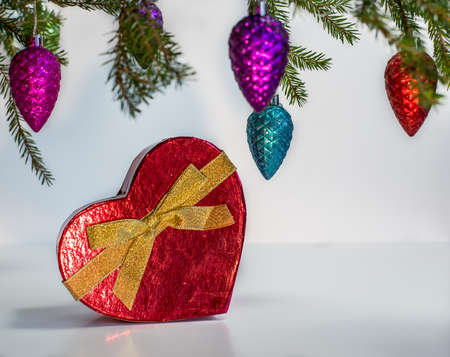 under heart: Red heart present under the Christmas tree - white background Stock Photo